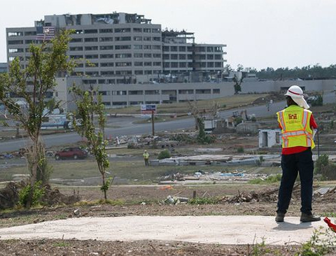 Bob Hill, a heavy mobile equipment mechanic with the U.S. Army Corps of Engineers' Philadelphia District, surveys the tornado-stricken landscape of the city during a break in debris removal operations. St. John's Regional Medical Center is visible in the background. Image courtesy of U.S. Army Corps of Engineers and Mark Haviland.